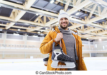 happy young man with ice-skates on skating rink - people,...