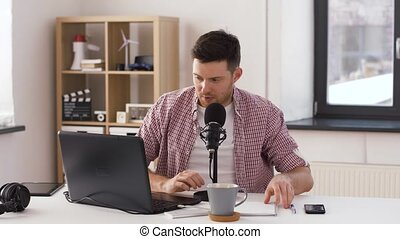 happy young man with laptop and microphone at home -...