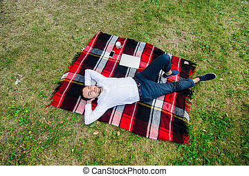 Happy young man with laptop relaxing on the grass, view from the top