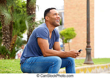 Happy young man with mobile phone sitting on sidewalk and looking away