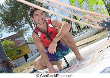 happy young man with security vest about to sail