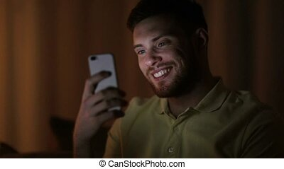 happy young man with smartphone at night