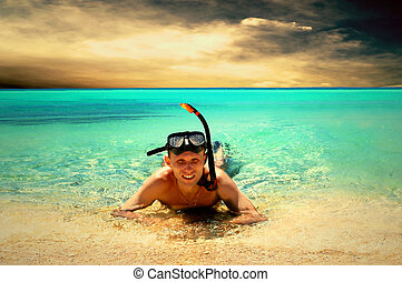 Happy young man with snorkeling on a sea beach