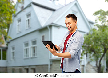 happy young man with tablet computer over house - real...