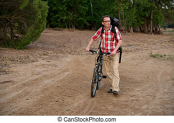 Happy young man with the bike, walking on the beach.