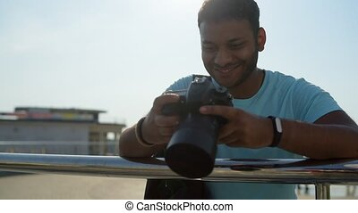 Happy young man with the camera leaning on the railing -...