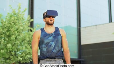 fitness, sport and technology concept - happy smiling young man with virtual reality headset or vr glasses outdoors