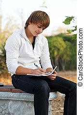 Happy Young man write in notebook, autumn outdoors - Young...