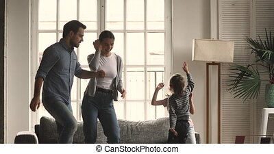 Happy young married couple dancing to music with children.