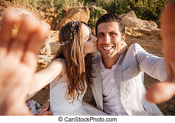 Happy young married couple making selfie at the beach