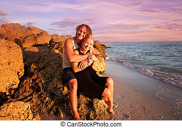 Happy Young Married Couple Sitting on Rocky Beach by the Ocean at Sunset