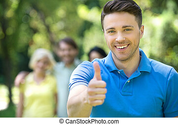 Happy young men outdoors. Cheerful young men showing his...