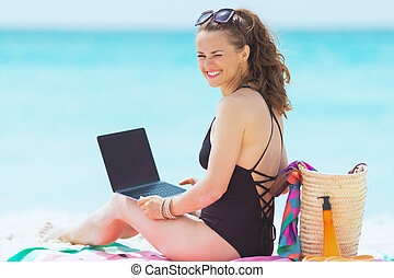happy young middle age woman on white beach working on laptop