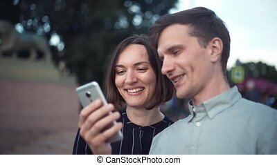 Happy young millennial couple watching videos on smartphone together in the park