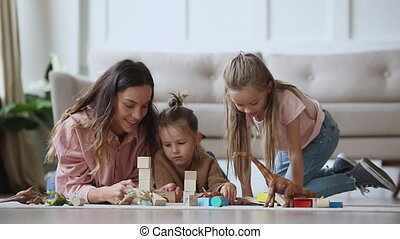 Happy young mixed race nanny babysitter lying on floor carpet with cute little preschool girls, playing toys together in living room. Smiling single mother enjoying playtime with two small children.