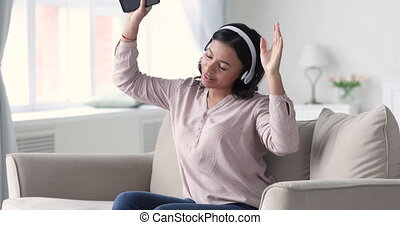 Happy young mixed race woman listening dancing to music. - ...