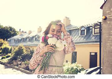 Happy young model in pink dress with flowers in hands on a background of city. Vintage toning effect