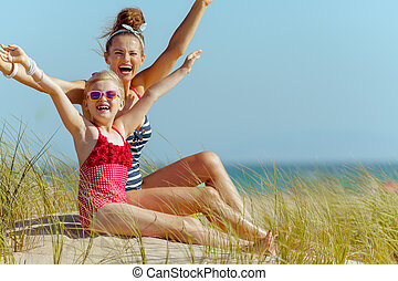 happy young mother and child in swimwear on beach rejoicing
