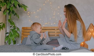 Happy young mother and her baby son playing togerher
