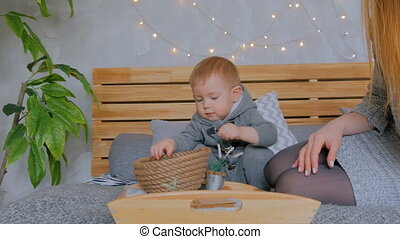 Happy young mother and her baby son playing with walnuts