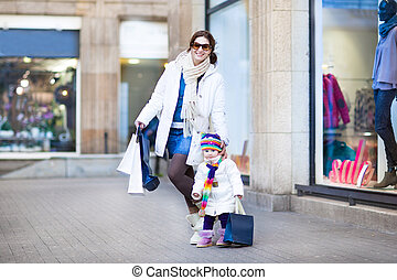Happy young mother and her cute toddler daughter enjoying...