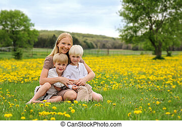 Happy Young Mother and Two Children Sitting in Flower Meadow