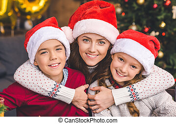 mother embracing with kids in santa hats