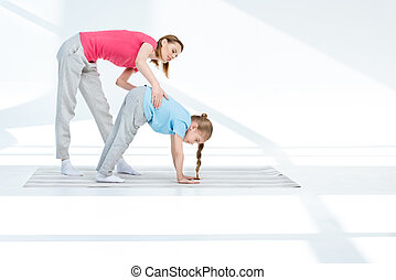 Happy young mother exercising with daughter on yoga mat
