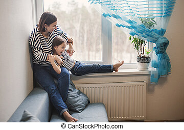 Happy young mother having fun with her little girl child at home