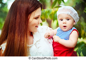 Happy young mother holding baby in park