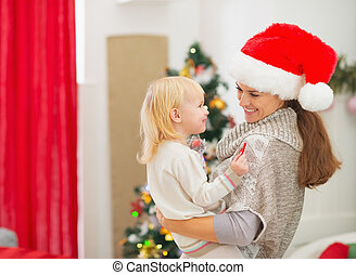 Happy young mother holding baby near Christmas tree