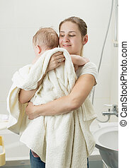 Happy young mother holding her baby after having bath