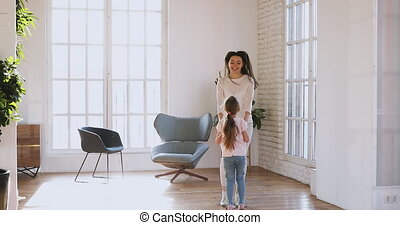 Happy young mother jumping with little child daughter.