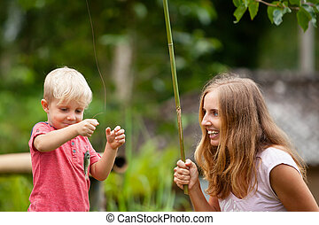 Happy young mother, little child fishing together with fun
