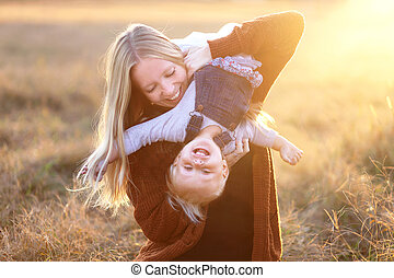 Happy Young Mother Playing with Baby Daughter Outside at Sunset
