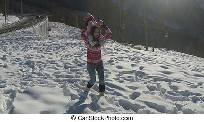 happy young mother playing with her daughter in the mountains in winter. slow motion