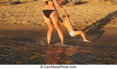 Happy young mother plays with her son in sea smiling and laughing.