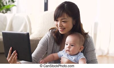 happy young mother with baby and tablet pc at home