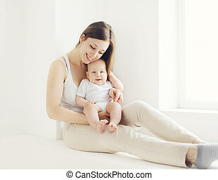 Happy young mother with baby at home in white room near window