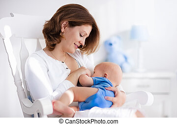 Happy young mother with baby boy at home - Young mother...