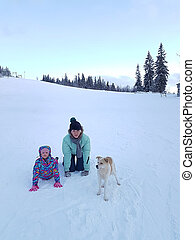 Happy young mother with daughter in the winter park with dog.