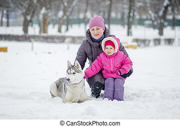 Happy young mother with daughter in winter park huskies dog