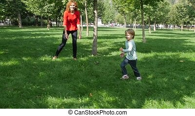Happy young mother with her daughter at park. Slow motion