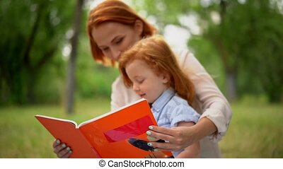 Happy young mother with her daughter reading outdoor
