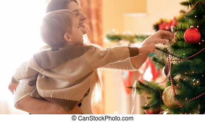 Happy young mother with her little boy decorating Christmas...