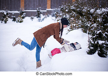 Happy young mother with her little cute daughter having fun in the backyard on a winter day