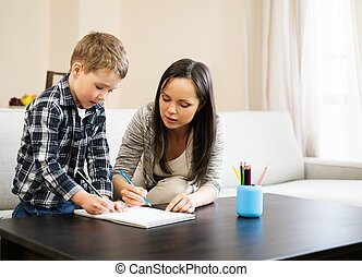 Happy young mother with her son drawing in home interior
