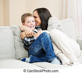 Happy young mother with her son on a sofa in home interior