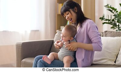 happy young mother with little baby boy at home