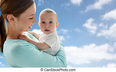 happy young mother with little baby over blue sky